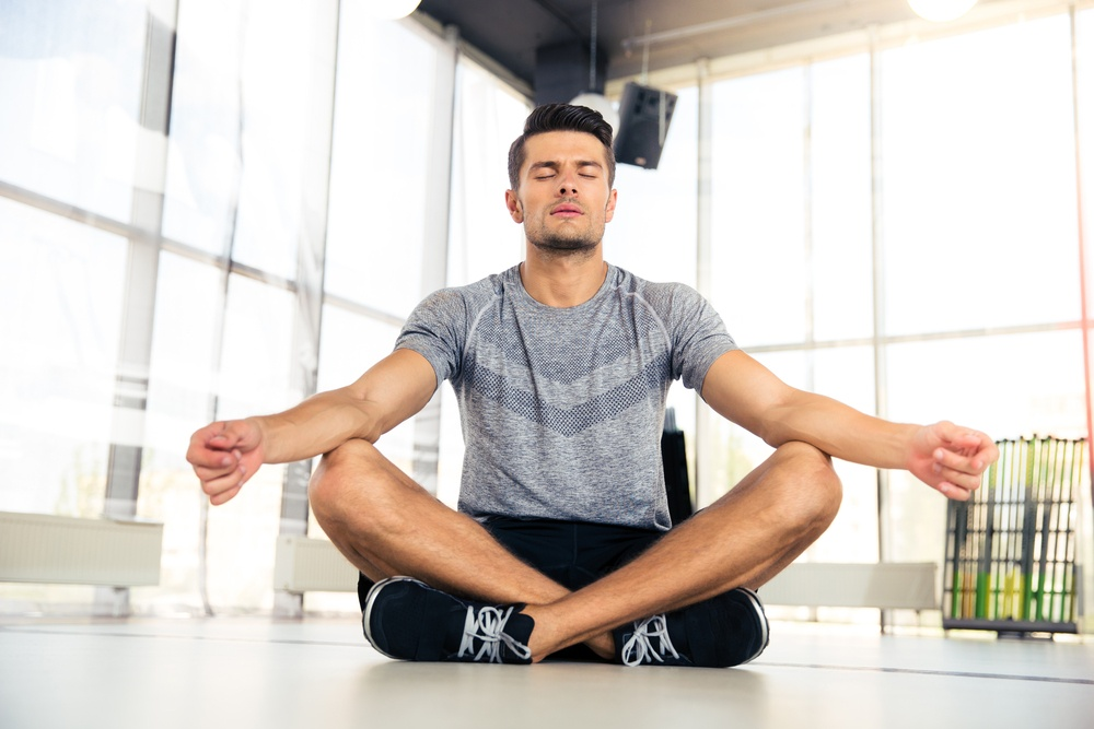 Portrait of a handsome man meditating in fitness gym.jpeg