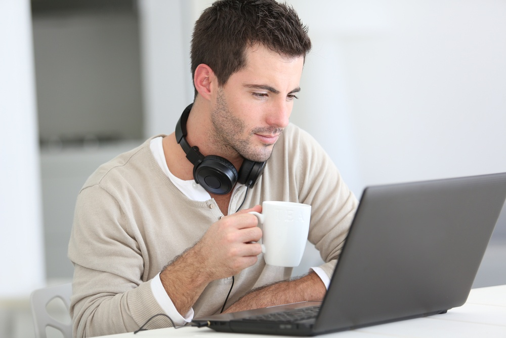 Man in front of laptop computer with headset.jpeg