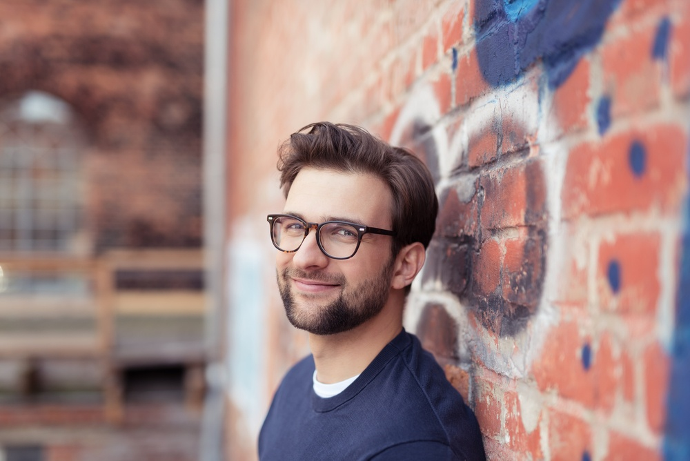 Portrait of Smiling Young Man with Facial Hair Wearing Eyeglasses and Leaning Against Brick Wall Painted with Graffiti.jpeg