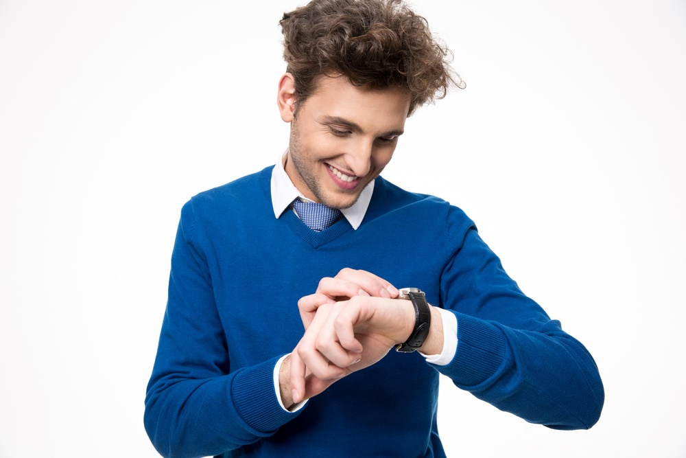 Happy businessman looking at watch over white background.jpeg